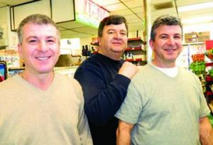 Ashmont Market: Peter, Harry, and John Georgoulopolous have worked side by side since 1984. The brothers sold the business to a new family on Monday, but plan to work there in the near term to help with the transition. Photo by Bill Forry
