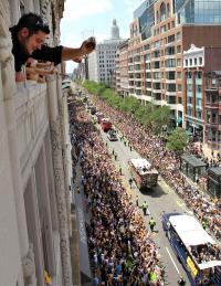 Toast of the town: Kostas Klokelis, from Framingham, Mass., toasts from a window overlooking the duck boats carrying the Boston Bruins and their families as they roll through downtown during a rally in celebration of their NHL hockey Stanley Cup playoff victory Saturday, June 18. AP Photo
