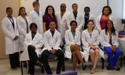 Medical Scholars on Bowdoin Street: Dr. Alphonso Brown, top row at center, is pictured with the 11 graduates of his inaugural Medical Scholars Program, ICAN, during a ceremony at the Bowdoin Street Health Center last Saturday, June 9. Photo by Sharon Ng