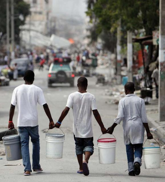 Haiti: Residents pitched in by carrying water in Port-au-Prince last Sunday as relief groups and officials focused on moving the aid flowing into Haiti to survivors of the powerful earthquake that hit the country on Tuesday. (AP Photo/Gregory Bull).