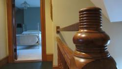 A lighthouse-inspired newel post outside a top-floor bedroom