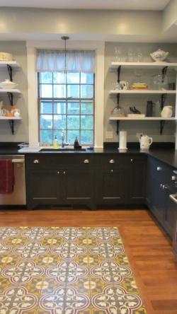 The modern kitchen still features the house's original glass windows