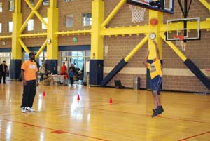 Salvation Army Kroc Center Fitness and Recreation Attendant Kenneth Heyward overseeing 10-year-old Jordan Edge of Dorchester as he participates in the Dribble, Dish & Swish basketball skills competition.