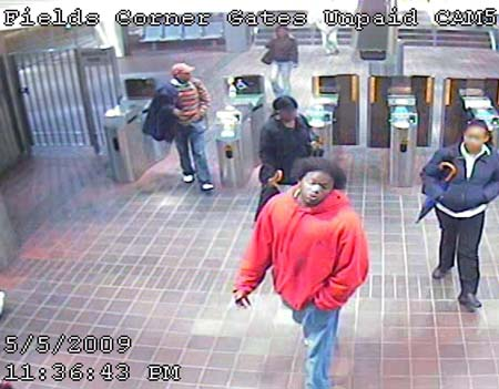 Person of interest: Boston Police think this man in red —shown at the Fields Corner T station on Tuesday — may be a suspect in a string of armed robberies. Police want to identify him and the woman holding an umbrella at right.