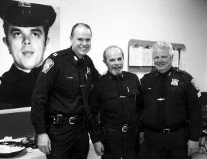 Boston Police Officer Paul Johnston, center, was flanked by Capt. Thomas Lee and Sgt. Herb White at Johnston's 2003 retirement party at Area C-11 stationhouse. At far left is a photo of a young Paul Johnston as a rookie patrolman. 			Reporter file photo