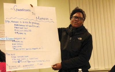 Mattapan Forum: Shavel'le Olivier of Mattapan, held a poster identifying concerns related to displacement and gentrification at a forum held at Mattapan Center for Life last Thursday. 	Caleb Nelson photo