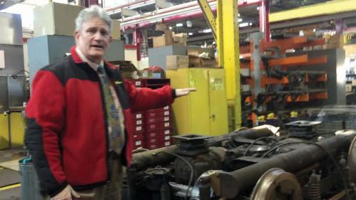 "Edward Belanger, maintenance supervisor of the MBTA's subway main repair facility in Everett, explains the components of the ""truck"" that is the propulsion unit that sits under the Mattapan PCC cars. On average, the MBTA repair crews receive one truck per month to re-build or repair. Bill Forry photo"