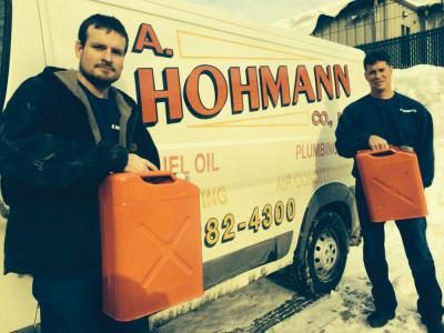Phil McIntyre and Teddy Hohmann of A. Hohmann Co. hold up the five gallon GI cans that have become essential to getting emergency fuel deliveries to customers whose fill pipes are too deeply buried in snow.   		  	Bill Forry photo