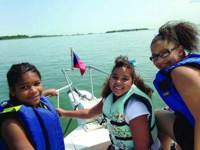 Cruisin' Dorchester Bay: Three members of the Boys and Girls Club of Dorchester enjoy the waters of the Boston Harbor thanks to the Dorchester Yacht Club.     Photo courtesy the Boys and Girls Club of Dorchester