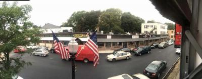A block of stores along Adams Street, shown to the right of the flags, have recently been acquired by new owners— John and Peter Lydon, who plan to make improvements to the storefronts. Bill Forry photo
