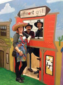 The Ashmont Grill booth at Sunday's Dot Day Chili Cook-off was built and painted in cooperation with DotArt. Pictured from left: Millie Rooney, Chris Douglass and Nuno Alves.	Photo by Ed Geary