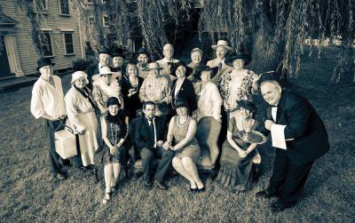 "The Dorchester Historical Society is hosting a ""Dinner at Willow Court"" tomorrow night (Sept. 26) at 6 o'clock at the society's headquarters at 195 Boston St. The DHS plans a festive evening to recall the style and elegance of earlier times: cocktails, a seated dinner, and a live auction. Period attire encouraged: Victorian, Edwardian, Roaring Twenties, upstairs or downstairs.  Proceeds to benefit the DHS Building Restoration fund. Board members and volunteers who dressed in Downton Abbey style for this photo include: Back row, from left: Richard O'Mara, Robert Severy, Gene Gorman, Kit Binns, Earl Taylor, Jeff Gonyeau. Middle row: Bill Loesch, Karen McNutt, Peggy Mullen, Emy Thomas, Anne Schmalz, Vicki Rugo, Terry Dolan, Rosanne Foley. Seated: Joyce Ellis, Joe Bagley, Jen Poulsen, Lianne Ames, and Paul Delorey.   Photo courtesy DHS, © Mike Ritter 2014"