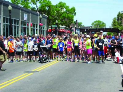 Runners line up in Fields Corner waiting for the pop of the starter's gun to begin the Dot Day 5K Road Race. Jacob Aguiar photo