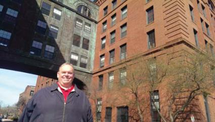 John Walsh : standing in front of his new Lower Mills digs.	Photo by Gintautas Dumcius