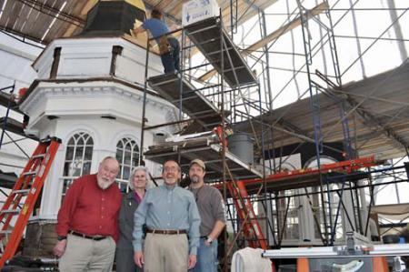Steeple chase: Former interim First Parish minister and board member Richard Kellaway, board chairperson Julie Simmons, Rev. Art Lavoie and Rich Friberg, project manager and instructor for the North Bennet Street School are shown inside the temporary workshop on Parish Street, where restoration carpentry students are working to finish the two lantern sections of the historic church's steeple. Photo by Bill Forry