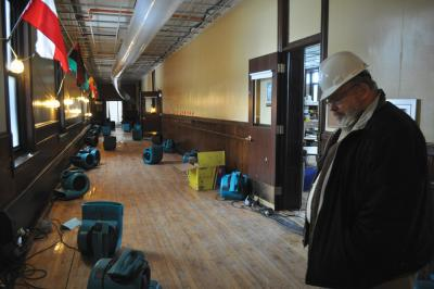 Rev. Jack Ahern surveyed the damage on the second floor of St. John Paul II Catholic Academy's Columbia campus on Monday morning.                                                                                        Bill Forry photo