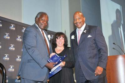 Gail Hobin (center) with UMass Boston Chancellor Dr. J. Keith Motley, right, and Vice-Chancellor Charlie Titus. 	Harry Brett photo