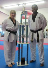 Taekwondo Duo: Amy Maillet and Master Fredson Gomes with the huge trophy won by MTC students in a recent tournament.