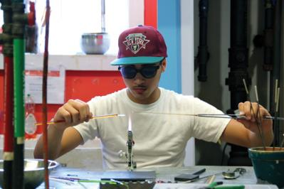 Bird Street Glass-blowers: Dany Melo, 15, makes glass beads as part of a glass-blowing program for boys through the Bird Street Community Center. Photo by Elizabeth Murray