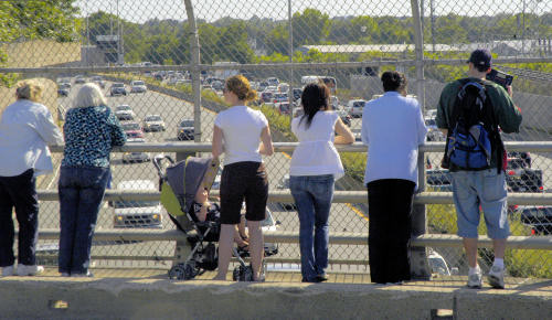 Waiting for the procession: Onlookers gather along the Savin Hill Avenue Bridge in Dorchester to view the funeral cortege. The scene was replicated all along the 75 mile  route form Hyannisport to Boston.