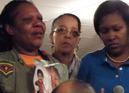 Mourning toddler: The grandmother of Amanihotp Smith,2, held up photos of the little boy at Morningstar Baptist Church. Photo by Adam Gaffin/Universal Hub