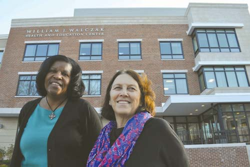 Codman's latest addition: Sandra Cotterell, CEO of the Codman Square Health Center, left and Meg Campbell, executive director of the Codman Academy Charter Public School, outside the newly-opened William J. Walczak Education and Health Center on Epping Street.
