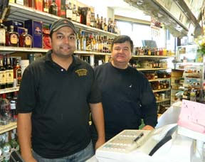 New owner, old owner: Jay Patel and Harry Gerogoulopolous split the watch behind Ashmont Market's main counter on Tuesday. Photo by Bill Forry