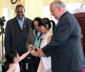 Valedictorian salute: A younger family member delivers a cell phone to Excel High School valedictorian Thao Nguyen as she received her award from Boston School Committee Chair Rev. Dr. Gregory G. Groover, Supt. Carol R. Johnson and Mayor Tom Menino. Photo by Elizabeth Murray