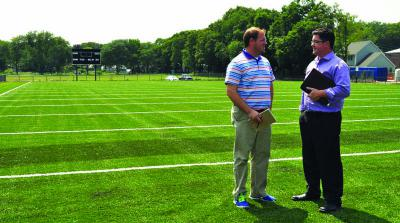 Almont's new gridiron: Interim Parks and Recreation Commissioner Chris Cook, left, and Ryan Woods, director of External Affairs for the department, are shown on the new football field at Almont Park. The Mattapan Patriots take the field on Friday. Photo by Bill Forry