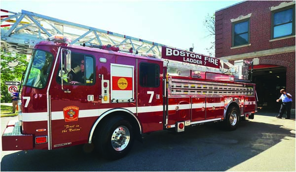 Firefighter Brian McKenna, aided by Firefighter Jeff Scott of Engine 17, backed in a new ladder truck: The Boston Fire Department welcomed four new fire ladders to its fleet on Saturday during an event at the fire house on Meetinghouse Hill. Chris Lovett photo