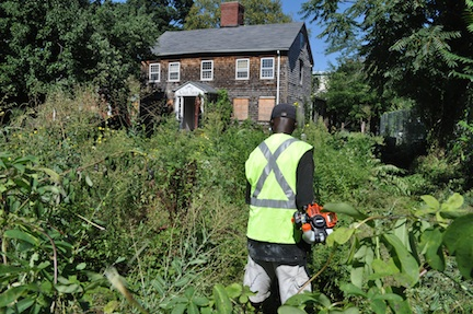 Worker clears brush on Fowler-Clark property