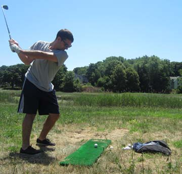 FORE!: During a week that offered a perfect stretch of summer weather for outdoor activities, Luke Baroski, above, and his friend Conor Farrell took turns Tuesday afternoon hitting golf shots from a makeshift driving range at Patten's Cove in Savin Hill. Photo b