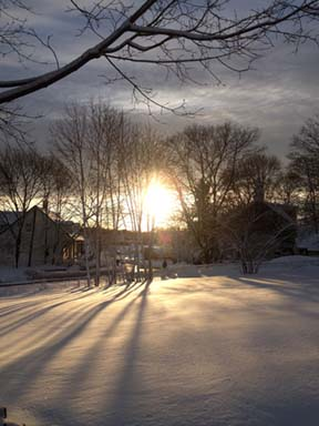 Snow-draped sunset on Sunday: Kenji Quinn snapped this shot from his home near River Street and Central Ave. in Lower Mills.