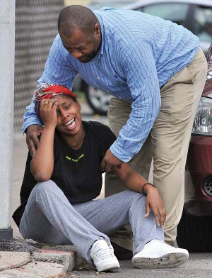 Chris Byner, who heads the city's Streetworker program, comforts grieving woman