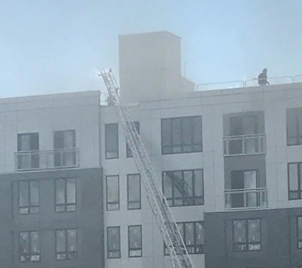 The first minutes of the June 28 fire on the top floor and roof of the Treadmark building were captured in this photo, which shows a firefighter on the roof. Polly O'Brien photo