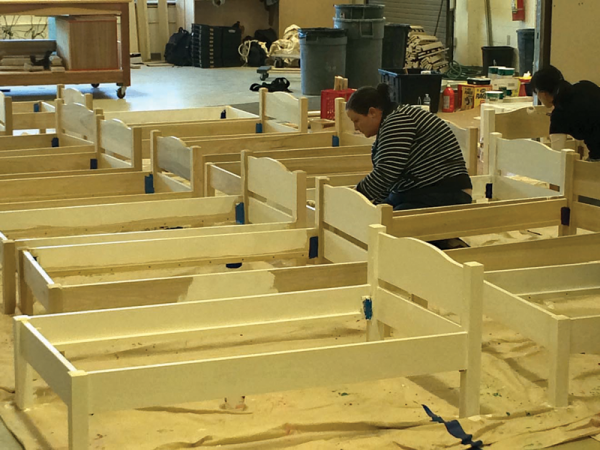 A volunteer helped to sand down recently built toddler beds at the New England R